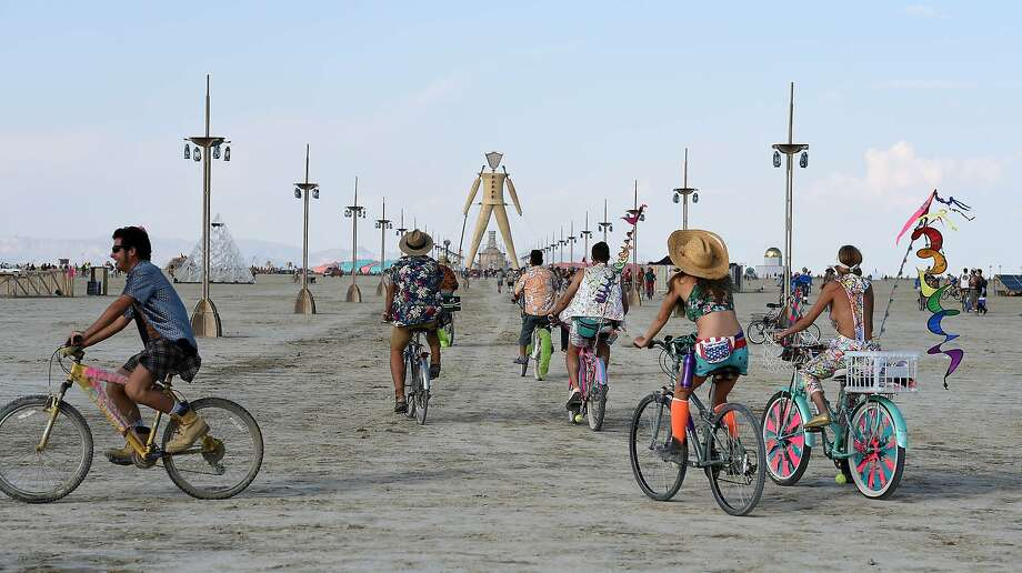 In this Monday, Aug. 25, 2014 photo, Burning Man participants bike on the playa during the annual Burning Man event on the Black Rock Desert of Gerlach, Nev. Photo: Andy Barron, Associated Press