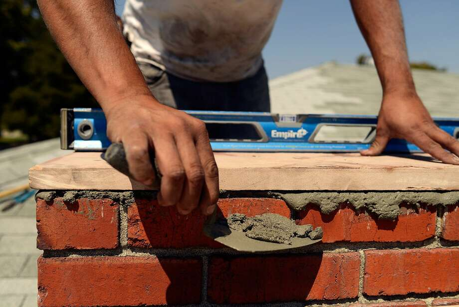 Daniel Macias attaches a stone slab to cap a chimney after removing the damaged upper section which resulted from Sunday's 6.0 magnitude earthquake in Vallejo, California, on August 25, 2014. Photo: Alvin Jornada, Special To The Chronicle