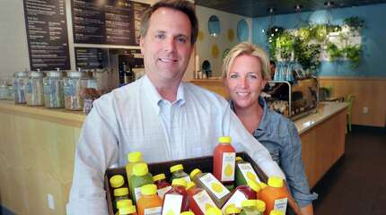 Husband and wife, Jeffrey and Cai Pandolfino, inside the restaurant they own, Green & Tonic, with a basket full of the cold-pressed juices they sell at their quick-service eatery that specializes in organic health food at 85 Railroad Ave., Greenwich, Wednesday, Aug. 27, 2014.