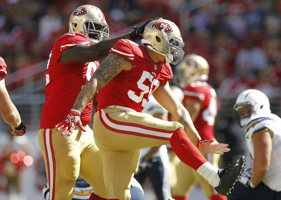 Quinton Dial congratulates Aaron Lynch (59) during Sunday's game against the Chargers. Photo: Mathew Sumner, Associated Press