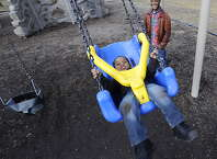 Jaden Francillon, 3 with the aid of his father Jean Albert Francillon swings high in Washington Park  in Albany, N.Y. Feb. 22, 2012.        ( Skip Dickstein / Times Union)