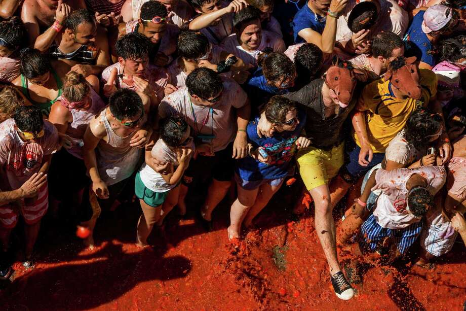 "Revellers take part in the annual ""tomatina"" festivities in the village of Bunol, near Valencia on August 27, 2013.  Some 22,000 revellers hurled 130 tonnes of squashed tomatoes at each other drenching the streets in red in a gigantic Spanish food fight known as the Tomatina.  Photo: GABRIEL GALLO, AFP/Getty Images / AFP"