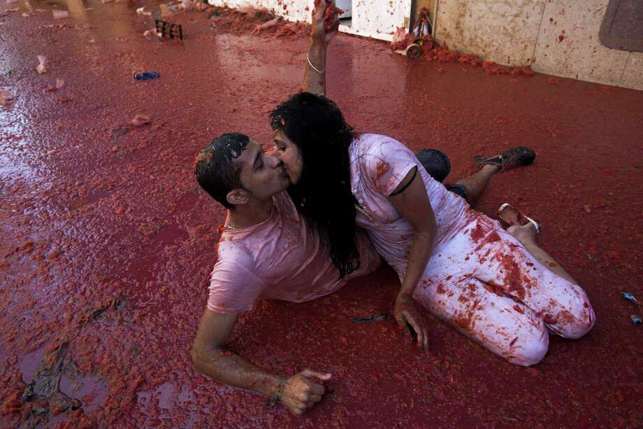 "A couple kisses during the annual ""tomatina"" festivities in the village of Bunol, near Valencia on August 28, 2013.  Photo: GABRIEL GALLO, AFP/Getty Images / AFP"