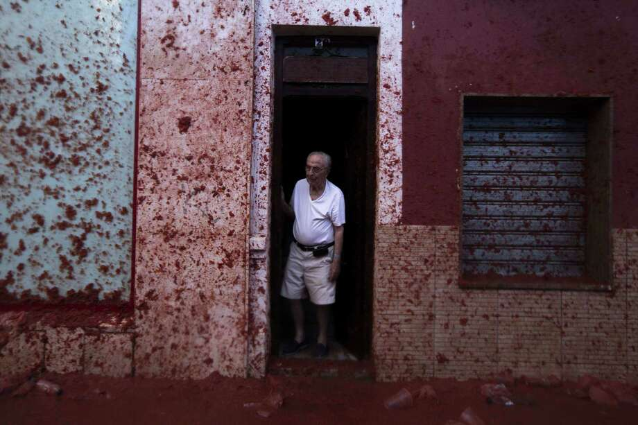 """A man stands in a doorway during the annual """"tomatina"""" festivities in the village of Bunol, near Valencia on August 28, 2013.  Photo: GABRIEL GALLO, AFP/Getty Images / AFP"""