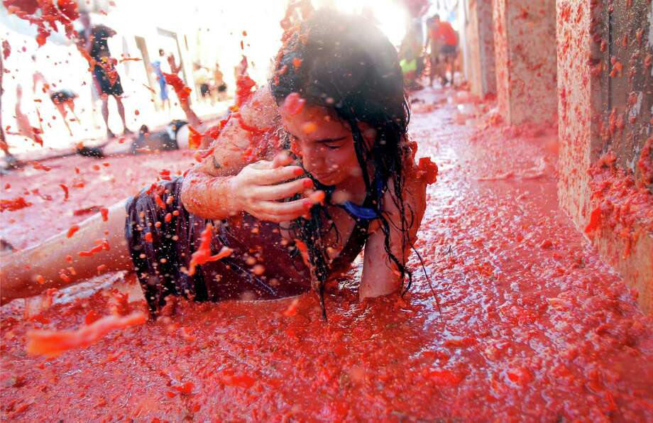 "A woman lays in a puddle of tomato juice during the annual ""tomatina"" tomato fight fiesta in the village of Bunol, 50 kilometers outside Valencia, Spain, Wednesday, Aug. 27, 2014.  Photo: Alberto Saiz, Associated Press / AP"