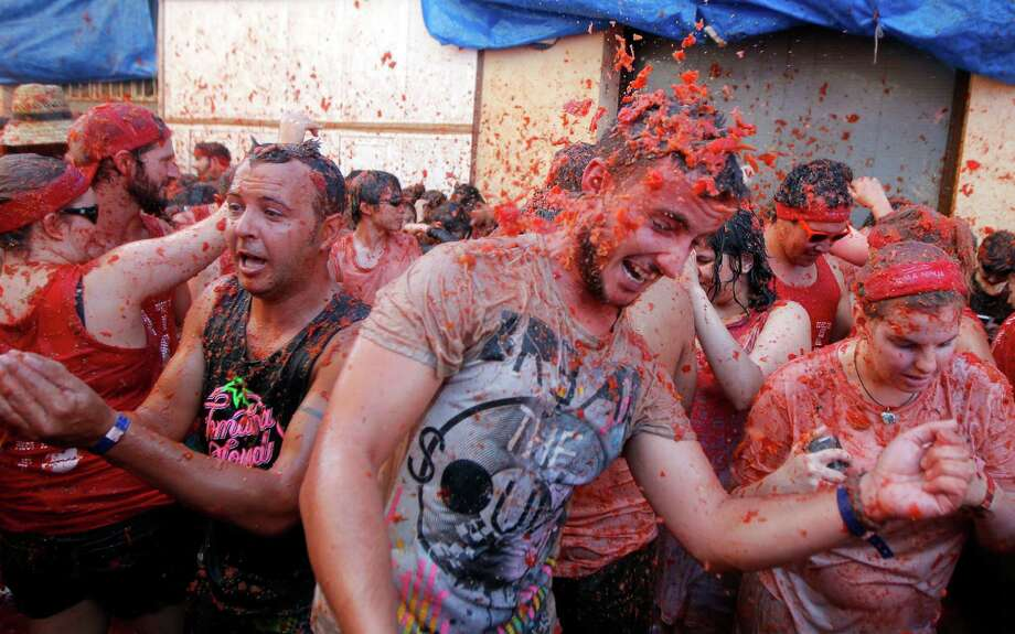 "People throw tomatoes at each other, during the annual ""tomatina"" tomato fight fiesta in the village of Bunol, 50 kilometers outside Valencia, Spain, Wednesday, Aug. 27, 2014.  Photo: Alberto Saiz, Associated Press / AP"