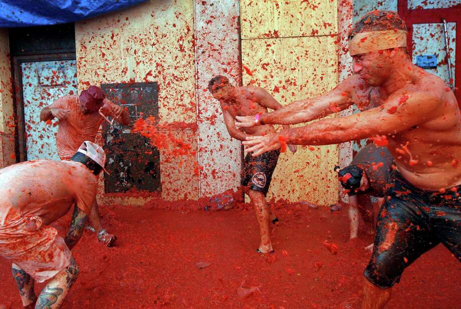 "Men throw tomatoes at each other, during the annual ""tomatina"" tomato fight fiesta in the village of Bunol, 50 kilometers outside Valencia, Spain, Wednesday, Aug. 27, 2014.  Photo: Alberto Saiz, Associated Press / AP"