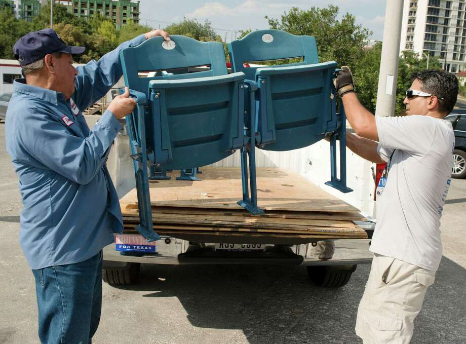 Volunteer Jesse Hernandez, right, helps Gilbert Barrera load seats into his truck, Wednesday, Aug. 27, 2014, at Alamo Stadium in San Antonio. Barrera plans to use the seats in a chapel he is dedicating to his son, who was killed in a traffic accident. (Darren Abate/For the Express-News) Photo: Darren Abate, San Antonio Express-News