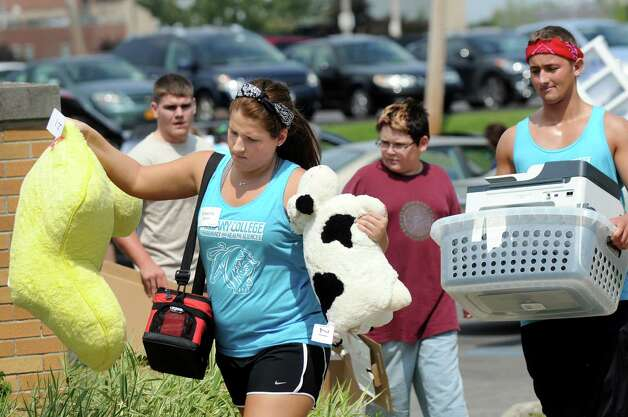 Orientation Committee member Breanne Spear, 19, center, helps carry belongings for freshmen moving into their dormitory rooms on Wednesday, Aug. 27, 2014, at Albany College of Pharmacy and Health Sciences in Albany, N.Y. (Cindy Schultz / Times Union) Photo: Cindy Schultz / 00028343A