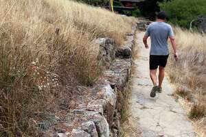 A jogger runs past a stone bench at the southern end of the Old St. Hilary's Open Space Preserve in Tiburon.