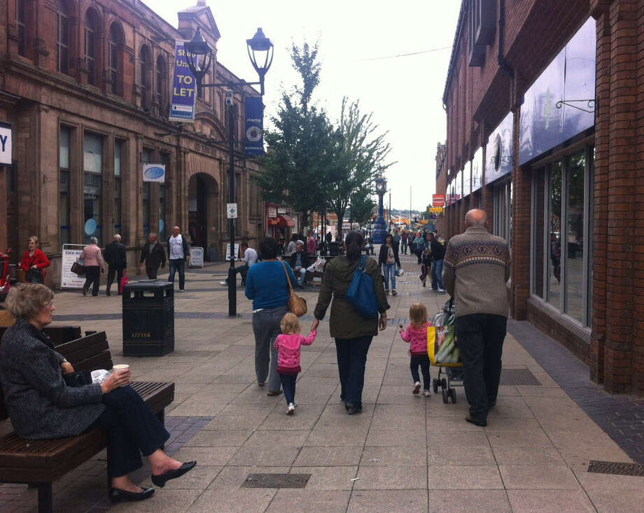People walk in the town center Wednesday in Rotherham, England, where 1,400 children were sexually exploited over 16 years, events that have shocked this English town. Photo: Sylvia Hui/Associated Press / AP