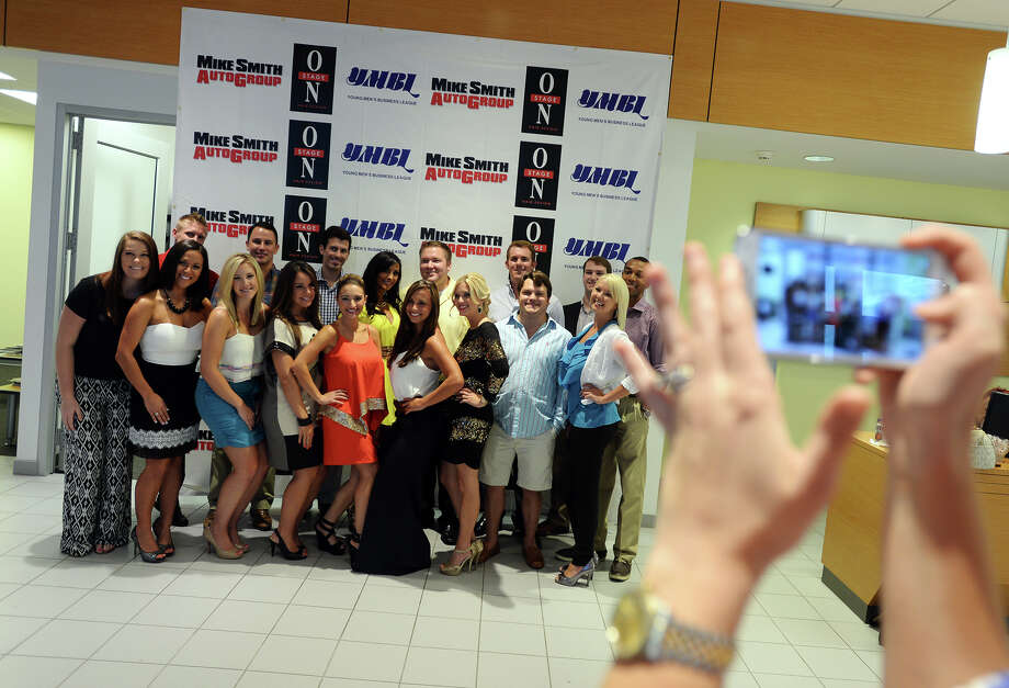 Bachelors and bachelorettes gather for a photo as Lauren Thieme lines up her shot during Wednesday's meet-and-greet. The 6th annual Ubi Caritas Date Auction held a media meet-and-greet at Mike Smith Nissan on Wednesday afternoon. The 21 bachelors and bachelorettes will be auctioning off unique packages on September 10 at Madison's on Dowlen, with all proceeds going to the Ubi Caritas Children's Health Education Initiative. For the last two years, the auction has raised over $100,000 each each. Photo taken Wednesday 8/27/14 Jake Daniels/@JakeD_in_SETX Photo: Jake Daniels / ©2014 The Beaumont Enterprise/Jake Daniels