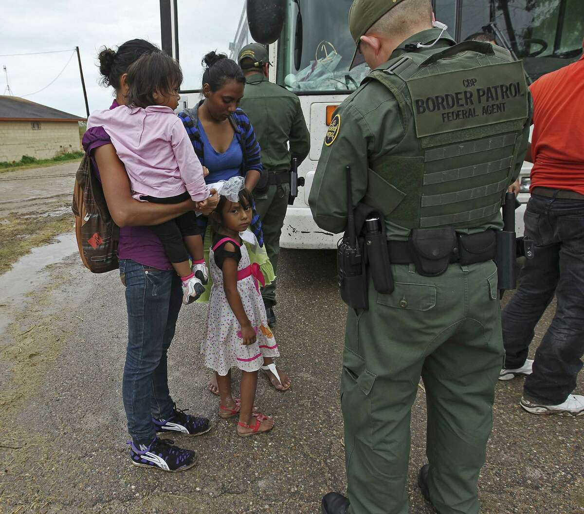 JUNE 25, 2014, 5:02 PM, GRANJENO, TEXAS 'Çô Immigrants wait to board a U.S. Government bus as Border Patrol agents process them in Granjeno, Texas. The city is just north of 'Ç£El Rincon del Diablo,'Ç¥ the Devil'ÇÃ?-s Corner, a hotbed of illegal border crossing on the Rio Grande by juvenile and mothers with children immigrants from Central