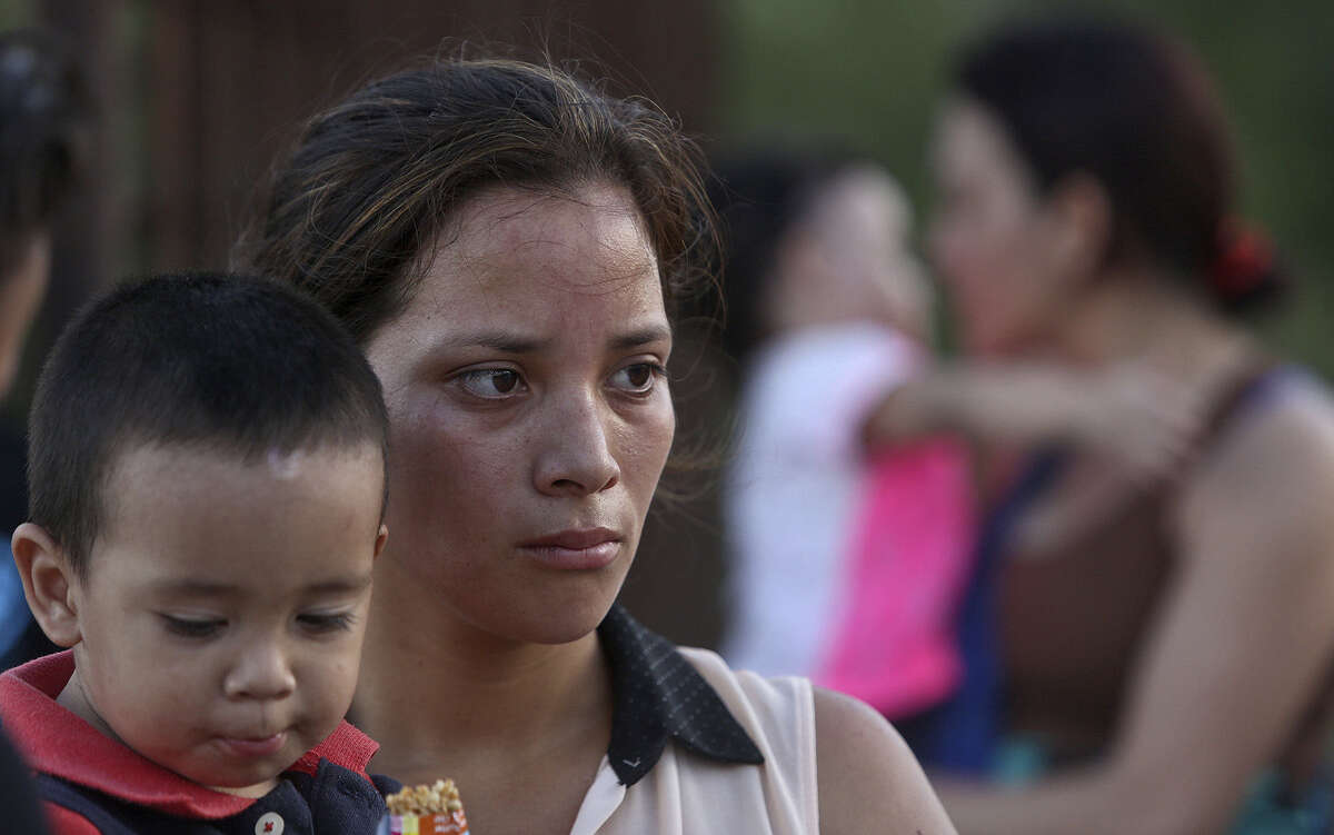 Maria Bertalina Ramirez, 21, of Honduras holds son, Jose Joel, 1, as they wait to be questioned by a U.S. Border Patrol agent after they crossed the Rio Grande by boat.