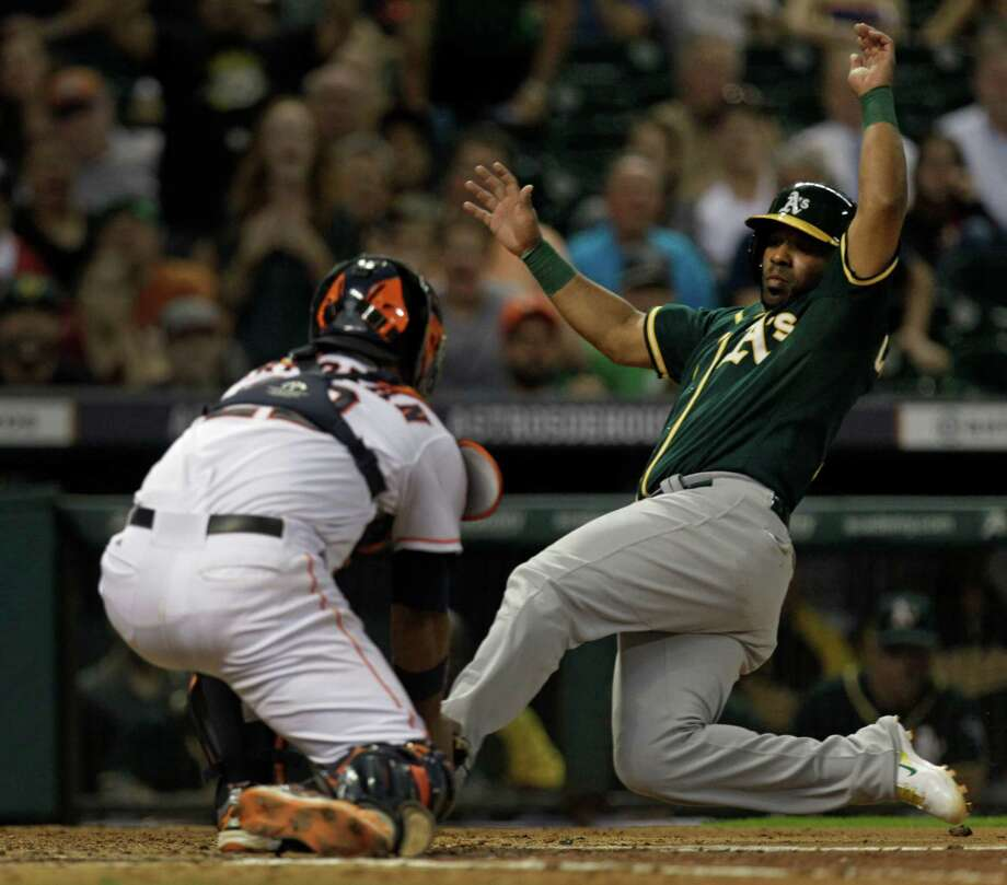 Astros catcher Carlos Corporan puts the tag on the A's Alberto Callaspo to help Brad Peacock maintain a shutout through the fifth inning. Peacock ran into some trouble in the sixth and was taken out of the game. Photo: Melissa Phillip, Staff / © 2014  Houston Chronicle