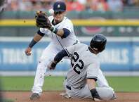 Detroit Tigers shortstop Eugenio Suarez, left, cannot handle the throw as New York Yankees' Jacoby Ellsbury (22) steals second base in the first inning of a baseball game in Detroit, Wednesday, Aug. 27, 2014. (AP Photo/Paul Sancya) ORG XMIT: MIPS105