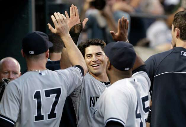 New York Yankees' Jacoby Ellsbury, center, celebrates after scoring on a Derek Jeter double against the Detroit Tigers in the third inning of a baseball game in Detroit Wednesday, Aug. 27, 2014. (AP Photo/Paul Sancya) ORG XMIT: MIPS108 Photo: Paul Sancya / AP