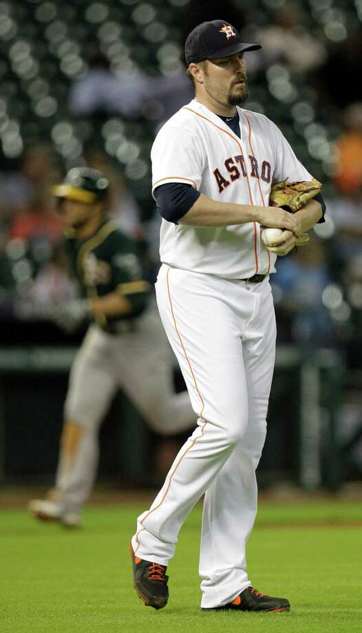 Houston Astros pitcher Chad Qualls walks to mound as Oakland Athletics Sam Fuld rounds the bases on his two run home run during the 9th inning at Minute Maid Park Wednesday, Aug. 27, 2014, in Houston. Coco Crisp also scored. Photo: Melissa Phillip, Houston Chronicle / © 2014  Houston Chronicle
