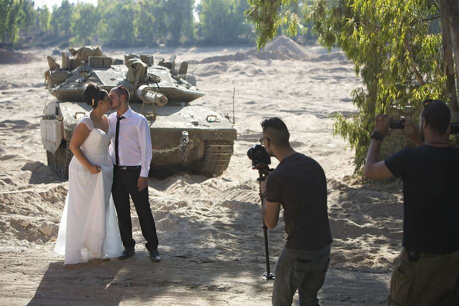 Israeli couple, Noga and Moshiko Siho, have their wedding photo taken in an army staging area on the Israeli Gaza border, near Kibbutz Yad Mordechai, Israel, Wednesday, Aug. 27, 2014. (AP Photo/Oded Balilty) Photo: Oded Balilty, Associated Press