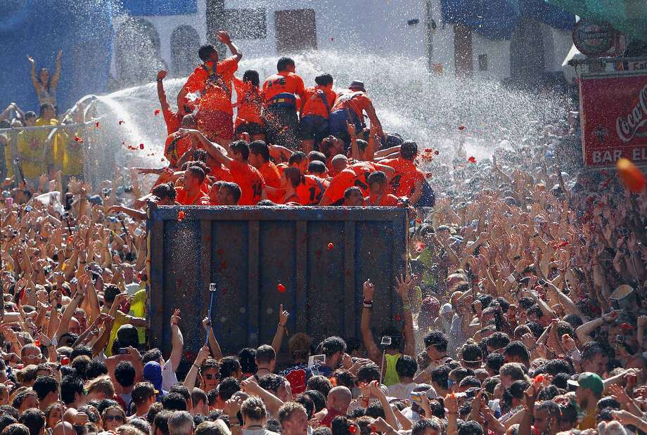 "Crowds of people throw tomatoes at each other, during the annual ""tomatina"" tomato fight fiesta, in the village of Bunol, 50 kilometers outside Valencia, Spain, Wednesday, Aug. 27, 2014. The streets of an eastern Spanish town are awash with red pulp as thousands of people pelt each other with tomatoes in the annual ""Tomatina"" battle that has become a major tourist attraction. At the annual fiesta in Bunol on Wednesday, trucks dumped 125 tons of ripe tomatoes for some 22,000 participants, many from abroad to throw during the hour-long morning festivities.  (AP Photo/Alberto Saiz) Photo: Alberto Saiz, Associated Press"