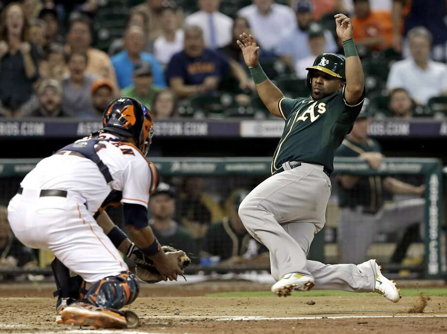 Oakland Athletics' Alberto Callaspo, right, slides toward home plate as Houston Astros catcher Carlos Corporan waits with the ball in the fifth inning of a baseball game Wednesday, Aug. 27, 2014, in Houston. Callaspo was out trying to score from first base on a Sam Fuld double. (AP Photo/Pat Sullivan) Photo: Pat Sullivan, Associated Press