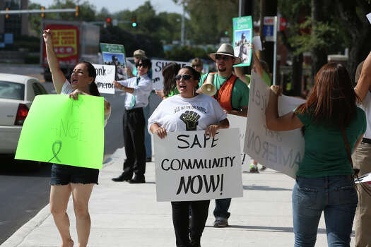 Signs are displayed to passing motorists as demonstrators stage a rally on Broadway to support the family of slain student Cameron Redus  on August 27, 2014. Photo: TOM REEL