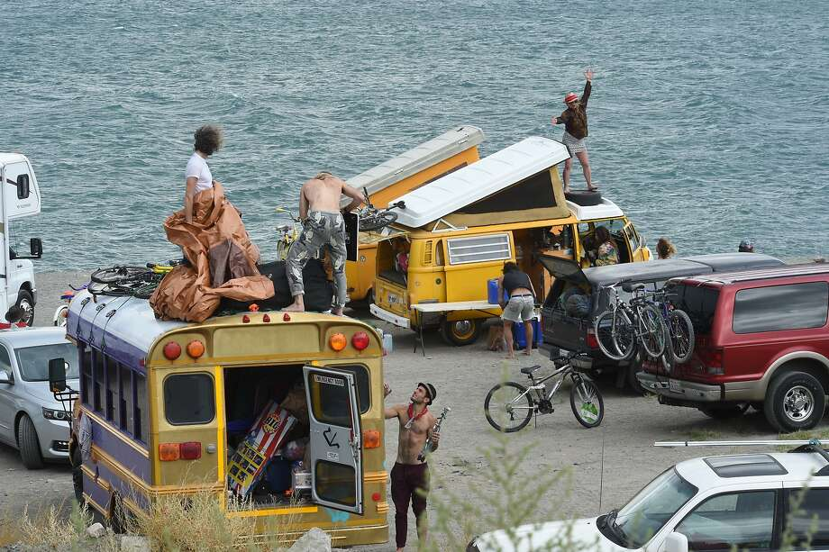 A woman dances on top of a van while other people set up camp on Blockhouse Beach at Pyramid Lake on Monday, Aug. 25, 2014, northeast of Reno, Nev. Thousands of Burning Man enthusiasts were on the outside looking in Monday after a rare batch of heavy rain forced organizers to temporarily close entry to the counterculture event in the desert 90 miles north of Reno. Many took advantage of the opportunity to camp at Pyramid Lake and made the best of the lake's beaches.  Photo: Tim Dunn, Associated Press