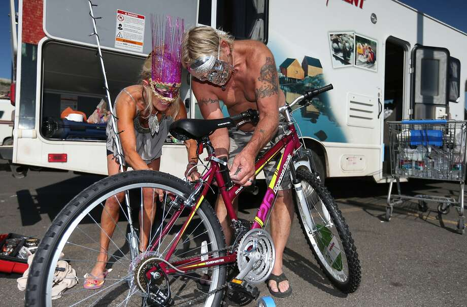 Karen Carner and her husband Mark Lee decorate a bike Tuesday, Aug. 26, 2014, at a Wal-Mart in Reno, Nev. The couple are providing concierge service for two women from Pittsburgh who are first-timers at the festival. Many Burners are delayed after a rare rain storm temporarily closed the entrance to Burning Man yesterday causing long traffic backups. The gates reopened at 6 a.m. Tuesday for the weeklong counter-culture festival that draws 70,000 people to the Black Rock Desert. Photo: Cathleen Allison, Associated Press