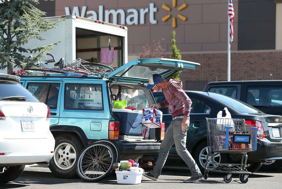 Burner Jake Pickle, of Encinitas, Ca., stocks up Tuesday morning, Aug. 26, 2014, at a Wal-Mart in Reno, Nev., after a rare rain storm temporarily closed the entrance to Burning Man yesterday. The Playa reopened at 6 a.m. for the week-long counter-culture festival that draws 70,000 people to the Black Rock Desert.  Photo: Cathleen Allison, Associated Press