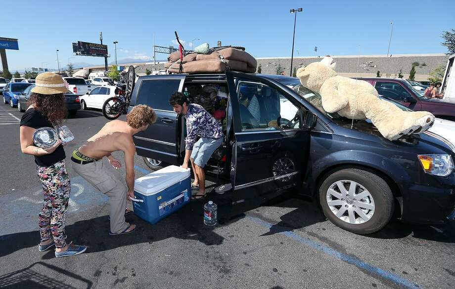 Burners, from left, Meyal Kashi, Avaid Furman and Ayal Moses, all from Isreal, stock up Tuesday, Aug. 26, 2014, at a Wal-Mart in Reno, Nev., after a rare rain storm temporarily closed the entrance to Burning Man yesterday. The Playa reopened at 6 a.m. for the weeklong counter-culture festival that draws 70,000 people to the Black Rock Desert. Photo: Cathleen Allison, Associated Press