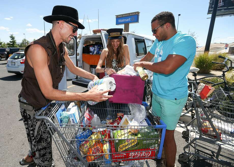 Burners, from left, Corbin Stinson, Beth Rademacher and Kaleb Acklin, all of Hawaii, stock up Tuesday morning, Aug. 26, 2014, at a Wal-Mart in Reno, Nev., after a rare rain storm temporarily closed the entrance to Burning Man yesterday. The Playa reopened at 6 a.m. for the weeklong counter-culture festival that draws 70,000 people to the Black Rock Desert. Photo: Cathleen Allison, Associated Press