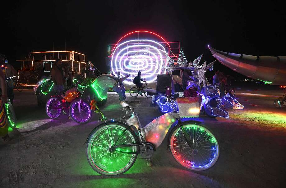 In this Sunday night, Aug. 23, 2014 photo, a Burning Man participant's bike is surrounded by art cars that are lined up at the Black Rock DMV to be registered at Burning Man on the Black Rock Desert of Gerlach, Nev. Photo: Andy Barron, Associated Press