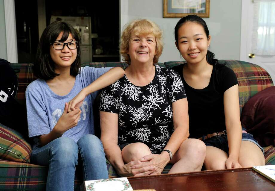 Ginny Schmidt-Gedney, center, has opened up her Danbury home to two exchange students from China. Left is Victoria Li, 13. Right is Lily Duan, 16. The girls are students at Immaculate High School in Danbury, Conn. Photo: Carol Kaliff / The News-Times