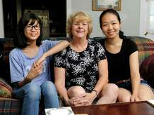 Ginny Schmidt-Gedney, center, has opened up her Danbury home to two exchange students from China. Left is Victoria Li, 13. Right is Lily Duan, 16. The girls are students at Immaculate High School in Danbury, Conn.