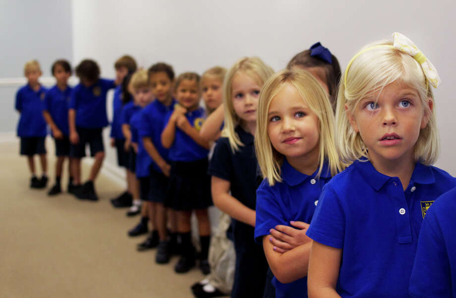 Katie Jane Klepko, right, stands with her kindergarten class while waiting to go outside for recess at Mason Classical Academy in Naples, Florida on Monday, Aug. 18, 2014. The new charter school, supported by Michigan-based Hillsdale College's Barney Charter School Initiative, opened its doors Monday to 414 students. (AP Photo/Naples Daily News, Carolina Hidalgo) Photo: Carolina Hidalgo, MBR / Associated Press / Naples Daily News