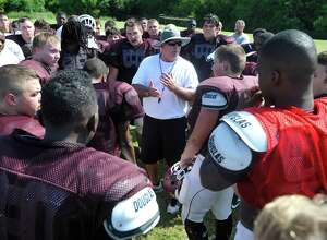 Head Coach Bobby McGallion, center,  talks with his players about what he wants in the coming days before he cuts them loose for the morning.   The Silsbee High School football team hit the field Friday August 9, 2013 in full pads.   Dave Ryan/The Enterprise
