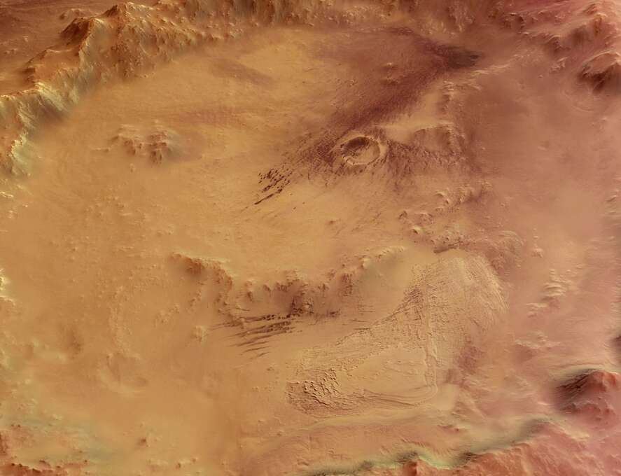 """The """"Smiley Face"""" - Crater Galle, lying to the east of the Argyre Planitia impact basin and south-west of the Wirtz and Helmholtz craters, at 51degrees South latitude and 329 degrees East longitude. The image clearly shows a large stack of layered sediments forming an outcrop in the southern part of the crater. Several parallel gullies, possible evidence for liquid water on the Martian surface, originate at the inner crater walls of the southern rim. Photo: Science & Society Picture Librar, SSPL Via Getty Images"""