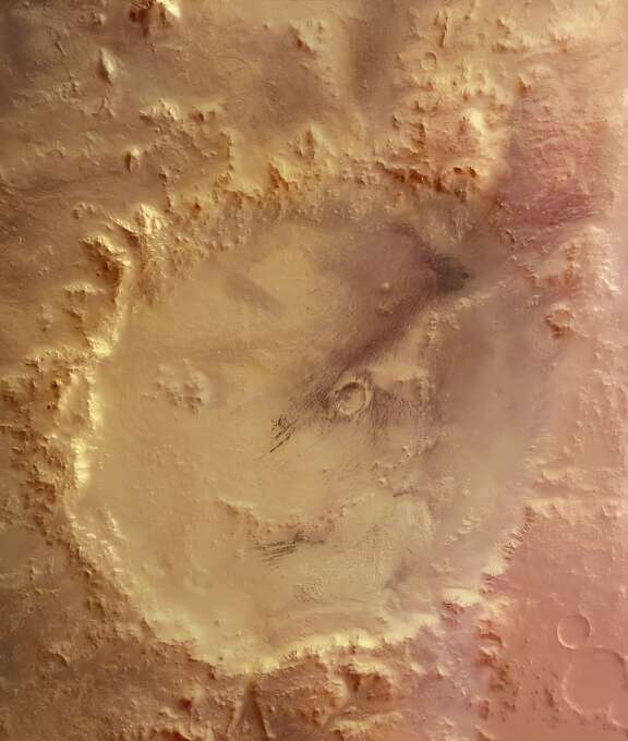 """The """"Smiley Face"""" - This image, obtained by the High Resolution Stereo Camera (HRSC) on the European Space Agency's Mars Express, is a mosaic of overlapping images gathered during five separate orbits. The ground resolution ranges between 10-20 metres per pixel, depending on location within the image strip, and the crater is shown lying near 51degrees South and 329 degrees East. North is up. The image shows Crater Galle containing a large stack of layered sediments forming an outcrop in the southern part of the crater. Several parallel gullies, possible evidence for liquid water on the Martian surface, originate at the inner crater walls of the southern rim.  (Photo by SSPL/Getty Images) Photo: Science & Society Picture Librar, SSPL Via Getty Images"""