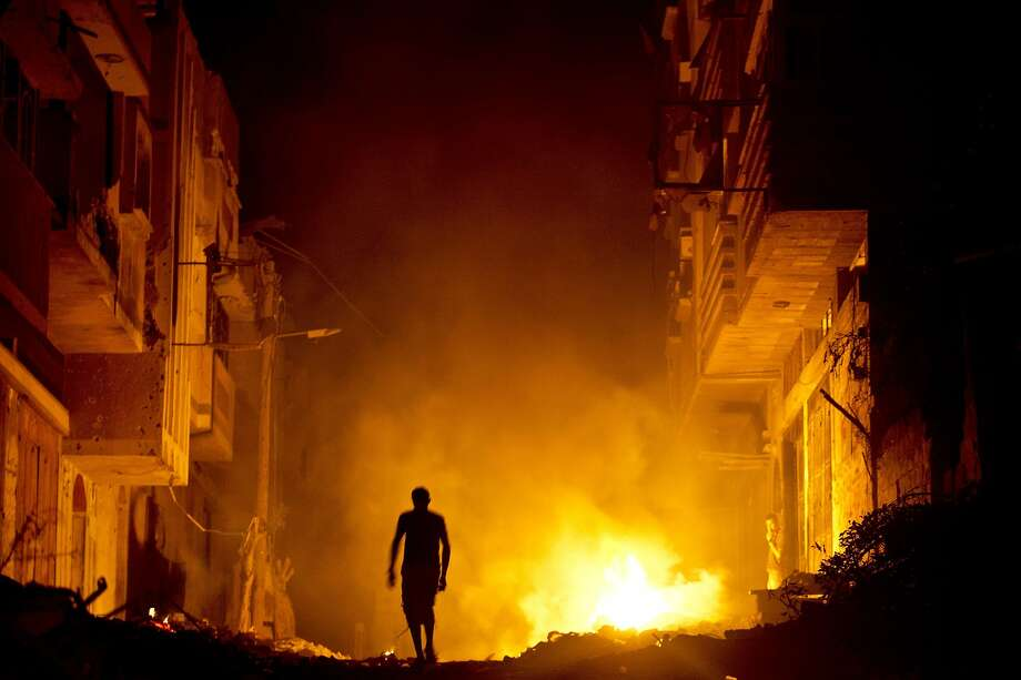 Skeeter repellent: A Palestinian man walks past a fire in a street set by a home owner in an effort to keep   mosquitoes away from their shattered homes in Shejaiya, Gaza Strip. Israel and Hamas both claimed   victory in the 50 days of fighting. Photo: Roberto Schmidt, AFP/Getty Images