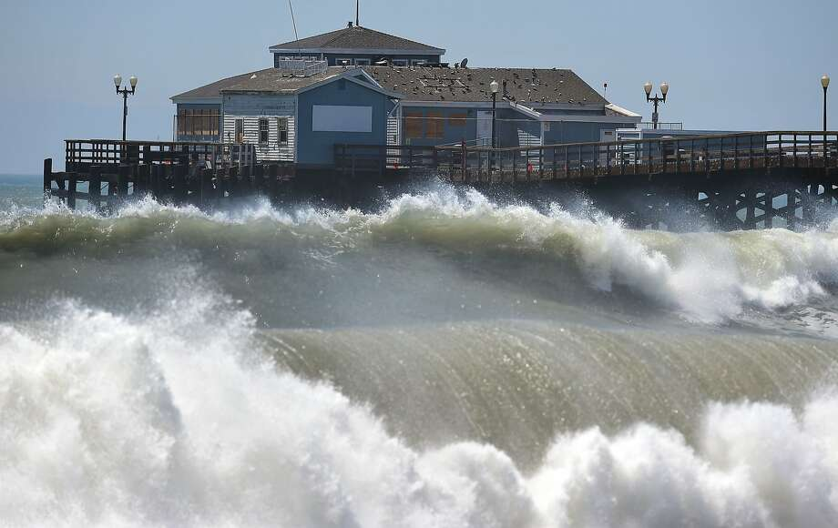 Big waves crash ashore and into the pier at Seal Beach, Calif., where an overnight ocean surge 