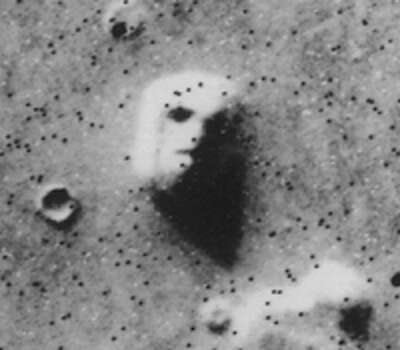 "Cropped version of the original batch-processed image (#035A72) of the ""Face on Mars"". The black dots that give the image a speckled appearance are data errors. Photo: Wikimedia Commons"