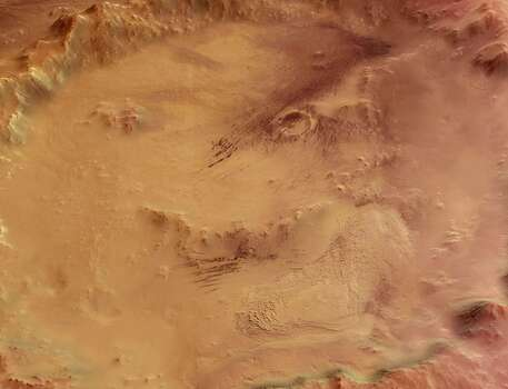 "The ""Smiley Face"" - Crater Galle, lying to the east of the Argyre Planitia impact basin and south-west of the Wirtz and Helmholtz craters, at 51degrees South latitude and 329 degrees East longitude. The image clearly shows a large stack of layered sediments forming an outcrop in the southern part of the crater. Several parallel gullies, possible evidence for liquid water on the Martian surface, originate at the inner crater walls of the southern rim. Photo: Science & Society Picture Librar, SSPL Via Getty Images"