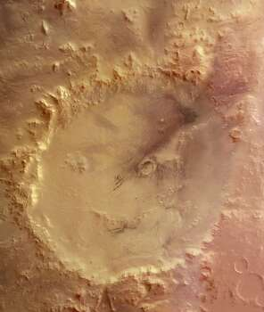 "The ""Smiley Face"" - This image, obtained by the High Resolution Stereo Camera (HRSC) on the European Space Agency's Mars Express, is a mosaic of overlapping images gathered during five separate orbits. The ground resolution ranges between 10-20 metres per pixel, depending on location within the image strip, and the crater is shown lying near 51degrees South and 329 degrees East. North is up. The image shows Crater Galle containing a large stack of layered sediments forming an outcrop in the southern part of the crater. Several parallel gullies, possible evidence for liquid water on the Martian surface, originate at the inner crater walls of the southern rim.  (Photo by SSPL/Getty Images) Photo: Science & Society Picture Librar, SSPL Via Getty Images"