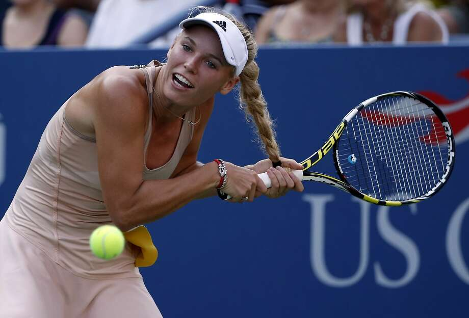 Woz's tail of woe: Caroline Wozniacki gets her hair tangled in her racket while returning a shot 