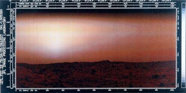 The image shows a red rock-strewn terrain with a pink sky. Two Viking spacecraft were launched towards Mars in 1975, each carrying a lander spacecraft and an orbiter. Both successfully landed their probes on Mars to study the Martian environment, soil constituents and to search for simple life forms - none were found. Photo: Science & Society Picture Librar, SSPL Via Getty Images