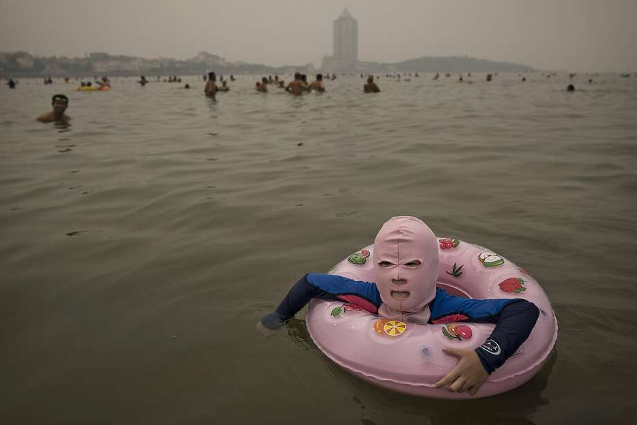 """At least it matches:A girl floating in the Yellow Sea in Qingdao, China, wears a """"facekini"""" to protect her from jellyfish stings, algae, the sun's ultraviolet rays, human companionship, life ... Photo: Kevin Frayer, Getty Images"""