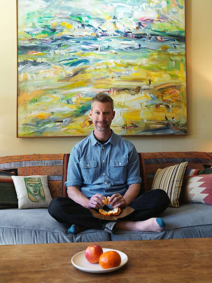 Rob Delamater, collector, artist and co-owner of Lost Art Salon in San Francisco, sits in the living room of his San Francisco apartment where the walls and halls are decorated with works by rediscovered artists. Photo: John Lee, Special To The Chronicle