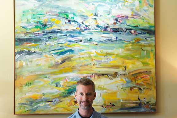 Rob Delamater, collector, artist and co-owner of Lost Art Salon in San Francisco, sits in the living room of his San Francisco apartment where the walls and halls are decorated with works by rediscovered artists.