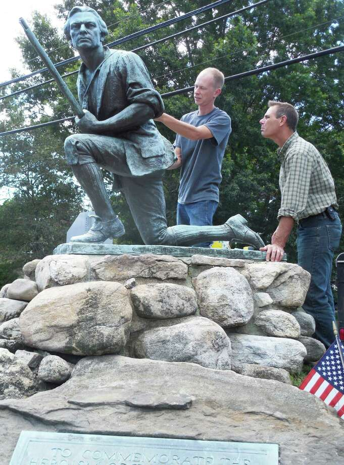 Francis Miller, right, the directing conservator and founder of ConservArt in Hamden, looks over the Minute Man statue as he and Michael Donovan, assistant conservator, begin restoration of the monument site. Photo: Anne M. Amato / westport news