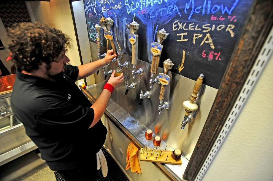 Graeme Bell pours a flight of all six beers on tap in the taproom at Galveston Island Brewing on August 16, 2014. Photo by Randy Edwards / @iamrandyedwards